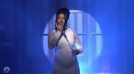 Cardi B confirms pregnancy rumors by showing off her baby bump in a skin-tight white gown on SNL