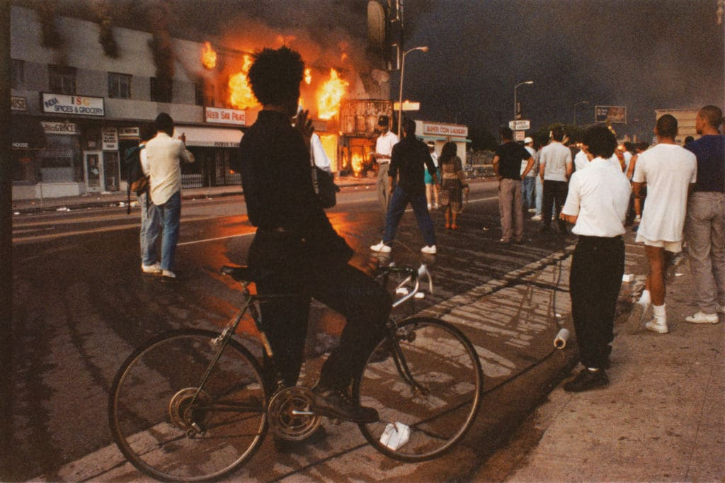 A view of businesses beginning to burn on Pico Boulevard near Hayworth Avenue, onlookers gathering, a young man dressed in black pausing on bicycle watching fire during the Rodney King Riots, and the sky black with smoke in daylight on April 30, 1992 in Los Angeles, California. (Photo by Lindsay Brice/Getty Images)