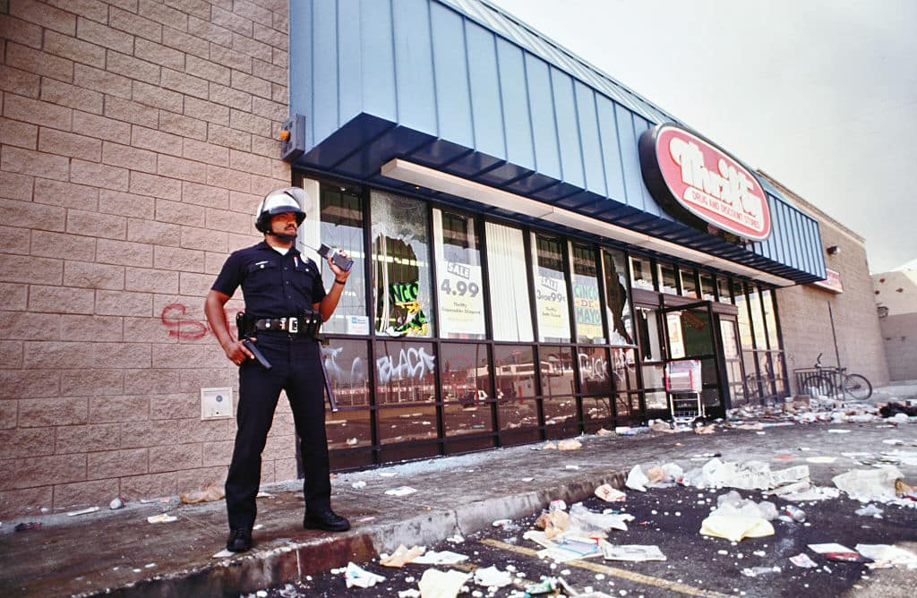 A lone LAPD officer keeps looters at bay from a Thrifty Drug and Discount store. Most of the store was cleaned out by looters. Los Angeles has undergone several days of rioting due to the acquittal of the LAPD officers who beat Rodney King. Hundreds of businesses were burned to the ground and over 55 people have been killed. (Photo by Ted Soqui/Corbis via Getty Images)