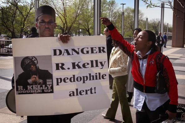 Dwight Taylor (L) of Gary Indiana is jeered by an R. Kelly supporter outside the Cook County courthouse where the R&B singer was due in court for the start of jury selection in his child pornography trial May 9, 2008 in Chicago, Illinois.  (Photo by Scott Olson/Getty Images)