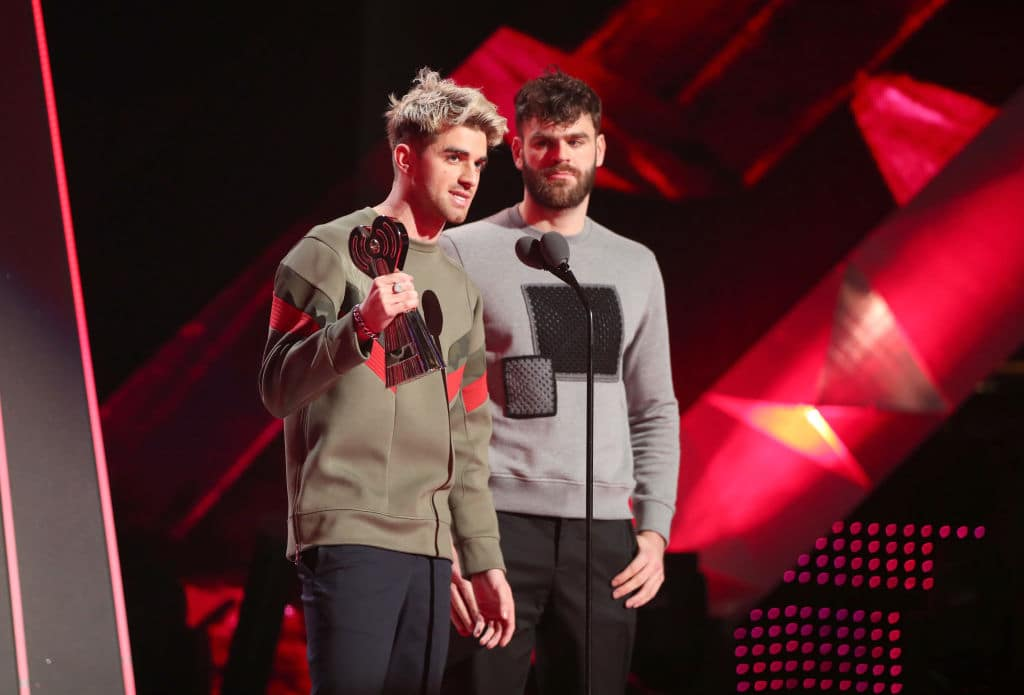 Andrew Taggart (L) and Alex Pall of The Chainsmokers speak onstage during the 2018 iHeartRadio Music Awards which broadcasted live on TBS, TNT, and truTV at The Forum on March 11, 2018 in Inglewood, California. (Photo by Christopher Polk/Getty Images for iHeartMedia)