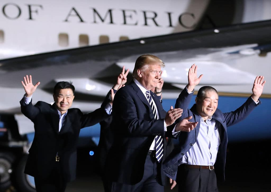 U.S. President Donald Trump walks with the three Americans just released from North Korea, Kim Dong Chul, Kim Hak-song and Tony Kim at Joint Base Andrews on May 9, 2018 in Maryland. (Photo by Mark Wilson/Getty Images)
