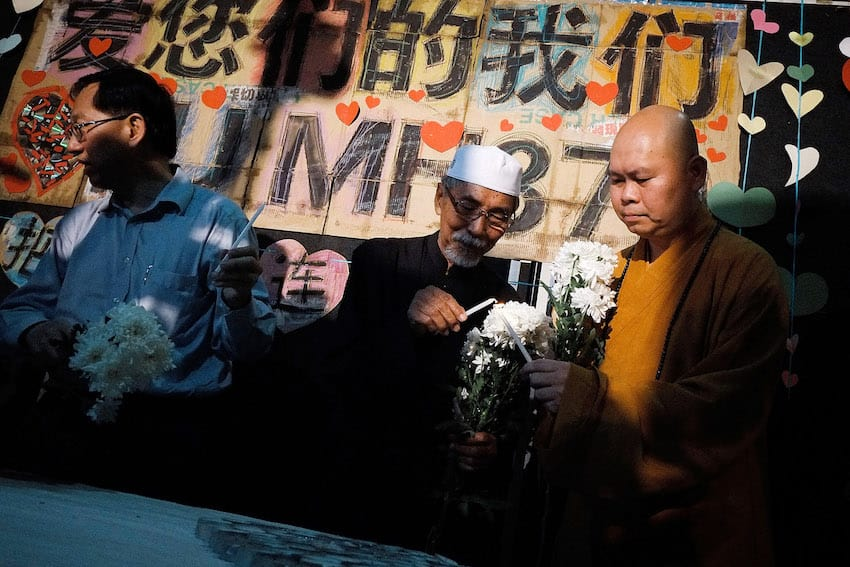 Representatives from Muslim, Buddhist and Christian religions light candles during a candlelight vigil to remember the victim of the ill-fated flight MH370 on March 30, 2014 in Kuala Lumpur, Malaysia. (Getty Images)