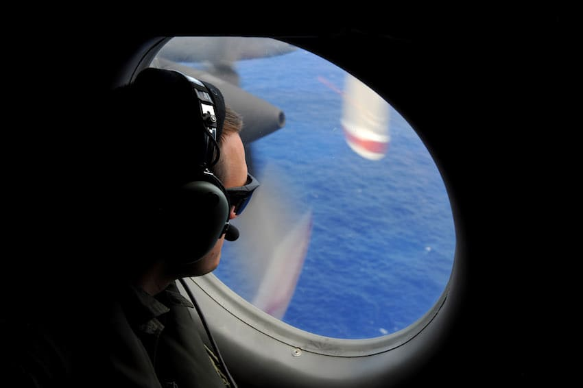 A crew member of a Royal New Zealand Airforce (RNZAF) P-3K2-Orion aircraft helps to look for objects during the search for missing Malaysia Airlines flight MH370 in flight over the Indian Ocean on April 13, 2014 off the coast of Perth, Australia. (Getty Images)