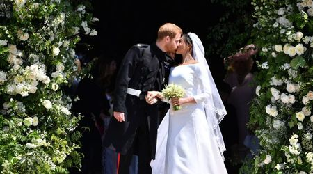 Breaking another tradition: Harry and Meghan do away with the balcony and kiss under floral archway instead