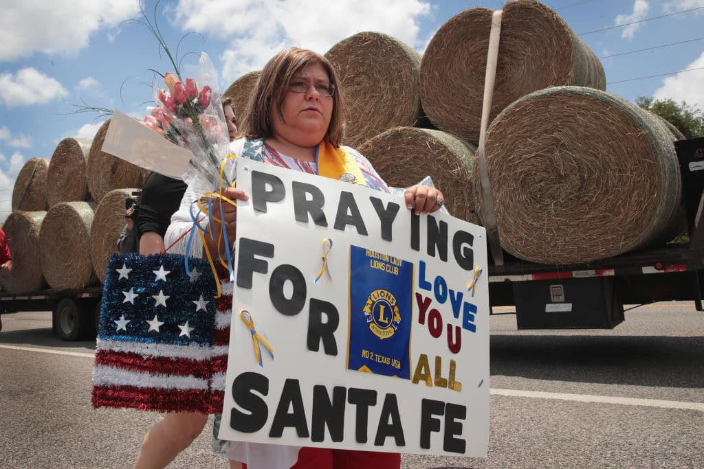 Lucy Gonzales carries a sign to be placed at a memorial outside of Santa Fe High School on May 19, 2018 in Santa Fe, Texas. (Photo by Scott Olson/Getty Images)