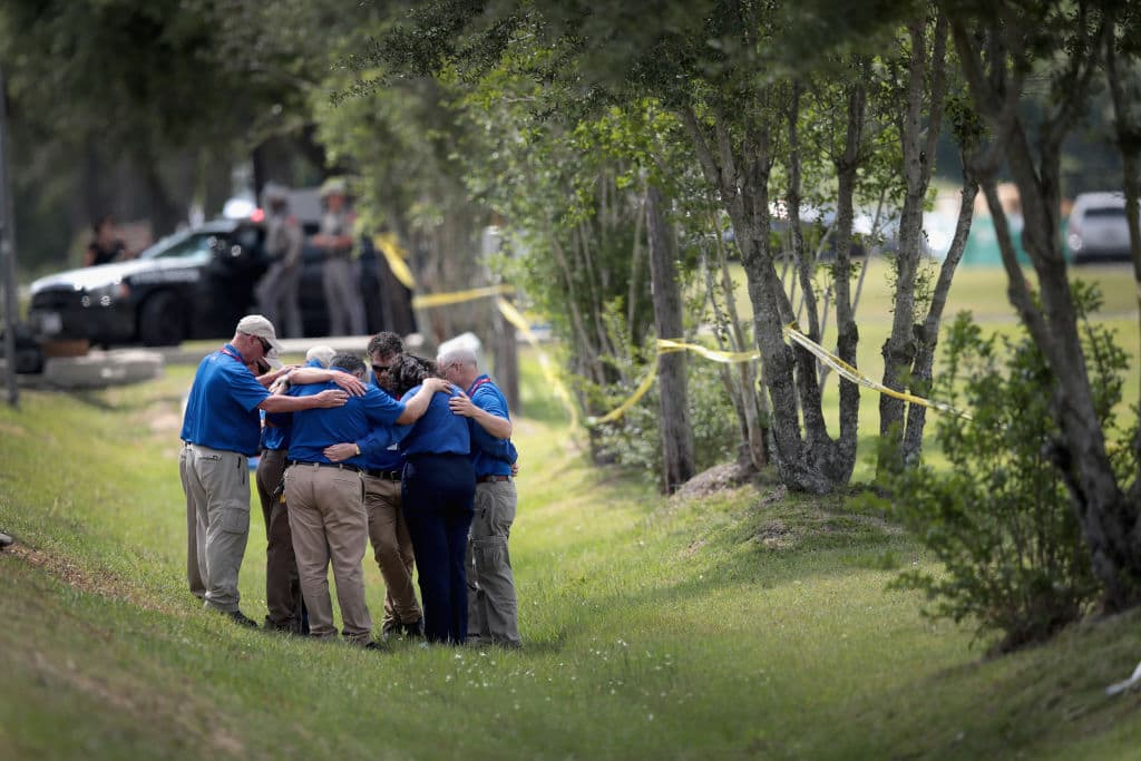 Members of a faith based organization pray alongside crime scene tape that surrounds Santa Fe High School on May 19, 2018 in Santa Fe, Texas. (Photo by Scott Olson/Getty Images)