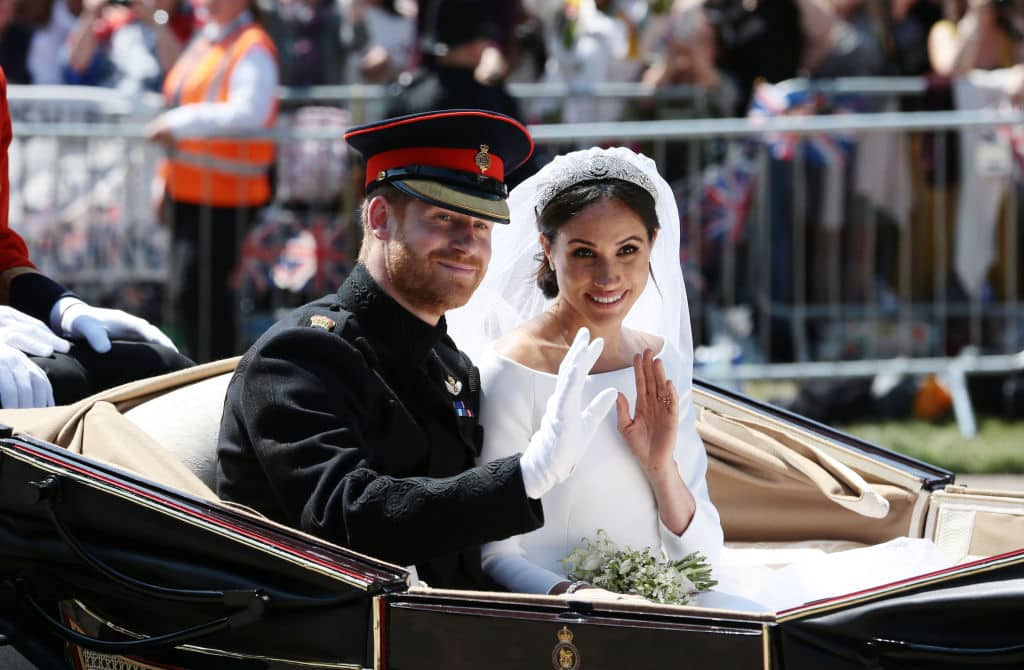 Prince Harry, Duke of Sussex and Meghan, Duchess of Sussex wave from the Ascot Landau Carriage during their carriage procession on Castle Hill outside Windsor Castle on May 19, 2018 in Windsor (Photo by Aaron Chown - WPA Pool/Getty Images)