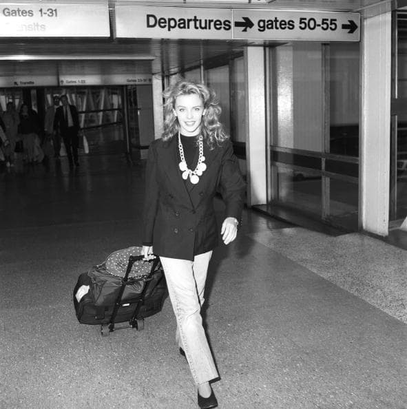 Kylie Minogue, actress and singer, pictured at Heathrow Airport as she arrived, along with the cast of Australian soap opera 'Neighbours', to appear at the Royal Variety Performance. London, 21 November 1988. (Getty Images)