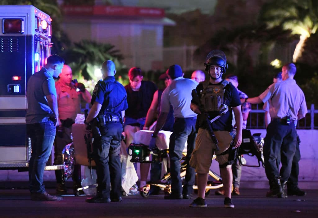 Police officers stand by as medical personnel tend to a person on Tropicana Avenue near Las Vegas Boulevard after the mass shooting (Getty Images)