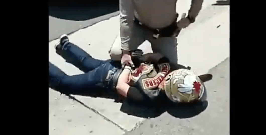 The biker lying face down after the hit as the cop puts handcuffs on him. (Twitter/screenshot)