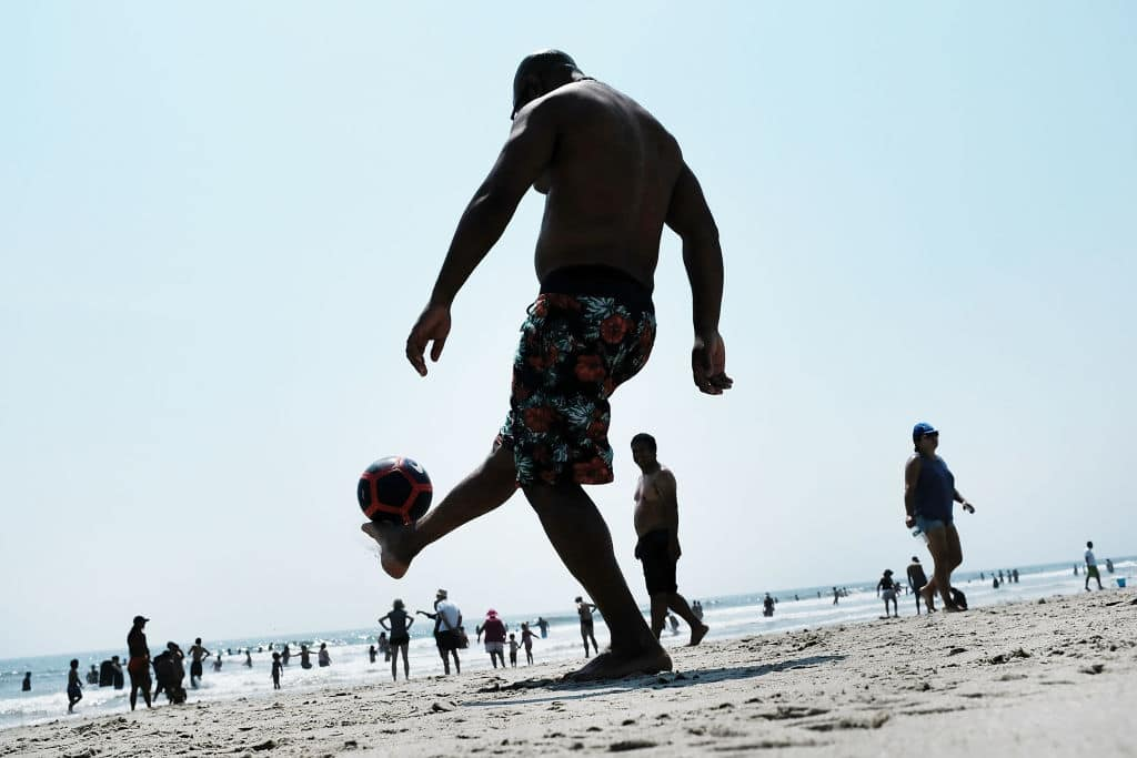 Men play soccer along Rockaway Beach as visitors try to stay cool on a hot summer day on August 22, 2017 in the Queens borough of New York City. (Getty Images)