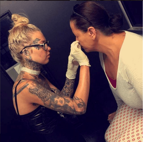 Luke, a body-piercer, at work with a client. (Instagram)