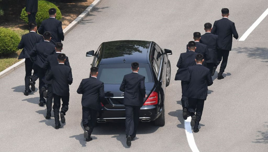 North Korean bodyguards jog next to a car carrying North Korea's leader Kim Jong-un returning to the North for a lunch break after a morning session of the inter-Korean summit on April 27, 2018 (Getty Images)
