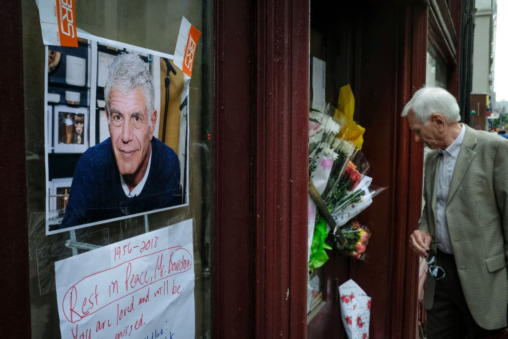 A man looks at notes and photographs left in memory of Anthony Bourdain at the closed location of Brasserie Les Halles, where Bourdain used to work as the executive chef, June 8, 2018 (Getty Images)