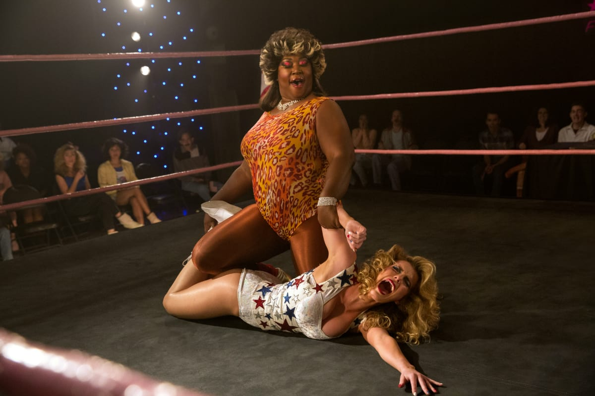 Kia Stevens who plays the Welfare Queen on 'GLOW' is a professional wrestler who appeared on Total Nonstop Action Wrestling under the ring name Awesome Kong. Pictured: Kia and Betty Gilpin, who portrays Liberty Belle (Netflix)