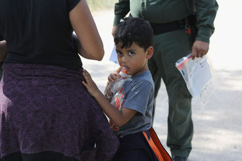 Central American asylum seekers wait as U.S. Border Patrol agents take them into custody on June 12, 2018, near McAllen, Texas. (Photo by John Moore/Getty Images)