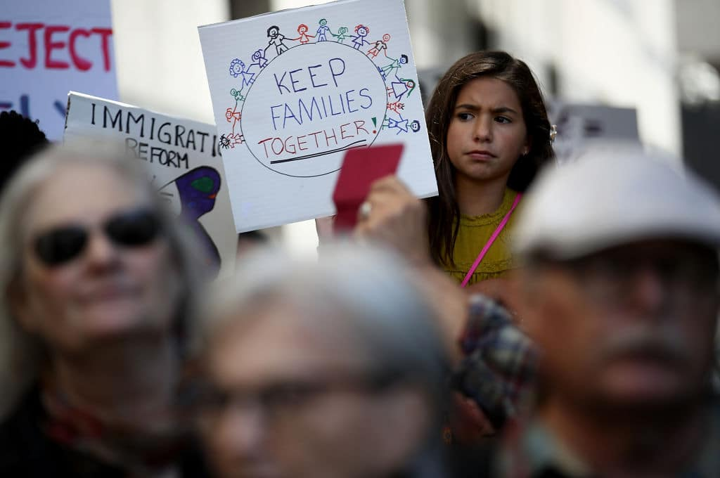 A young girl holds a sign during a demonstration outside of the San Francisco office of the Immigration and Customs Enforcement (ICE) on June 19, 2018 in San Francisco, California. (Getty Images)