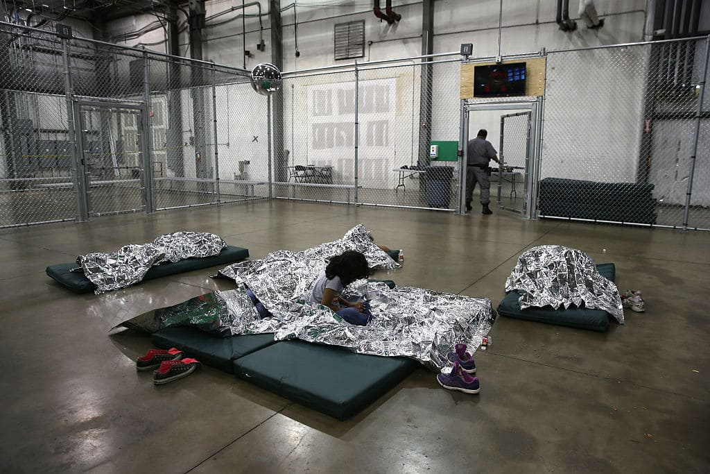 A girl from Central America rests on thermal blankets at a detention facility run by the U.S. Border Patrol on September 8, 2014, in McAllen, Texas. The Border Patrol opened the holding center to temporarily house the children after tens of thousands of families and unaccompanied minors from Central America crossed the border illegally into the United States during the spring and summer. (Photo by John Moore/Getty Images)
