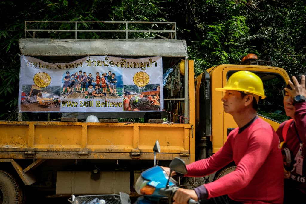 A banner hangs on the rescue shuttle bus with the photos of the missing children and their coach & the hashtag 'WE STILL BELIEVE' outside of Tham Luang Nang Non cave on July 04, 2018 in Chiang Rai, Thailand (Photo by Linh Pham/Getty Images)