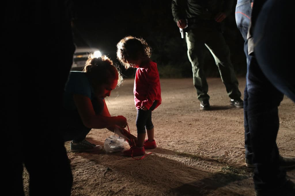 A Honduran mother removes her two-year-old daughter's shoe laces, as required by U.S. Border Patrol agents, after being detained near the U.S.-Mexico border on June 12, 2018 in McAllen, Texas. (Getty Images)