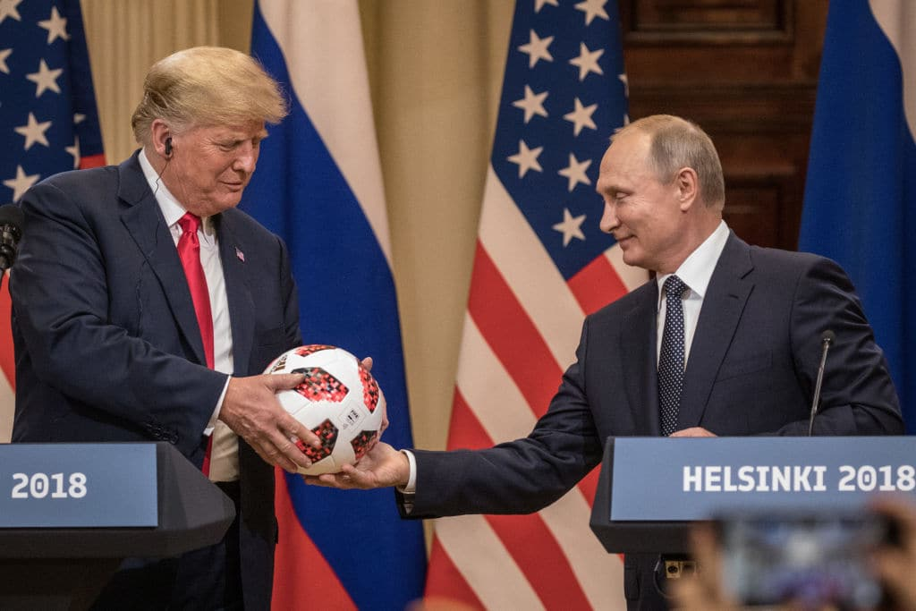 Russian President Vladimir Putin hands U.S. President Donald Trump (L) a World Cup football during a joint press conference after their summit on July 16, 2018 in Helsinki, Finland. (Getty Images)
