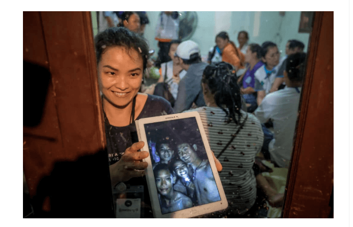 Relatives of the missing boys show photos of them after the 12 boys and their soccer coach have been found alive in the cave in Chiang Rai, Thailand. (Getty Images)