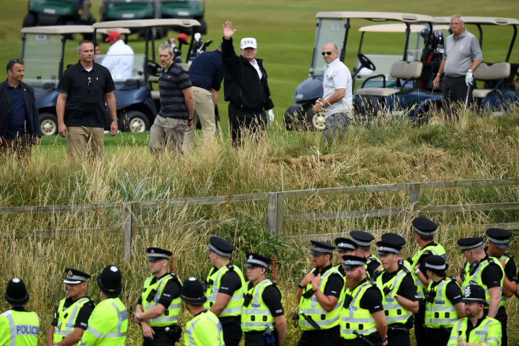 Police secure the area as U.S. President Donald Trump, wearing a hat with Trump and USA displayed on it, waves while playing golf at Trump Turnberry Luxury Collection Resort during the President's first official visit to the United Kingdom on July 14, 2018 in Turnberry, Scotland. (Getty Images)