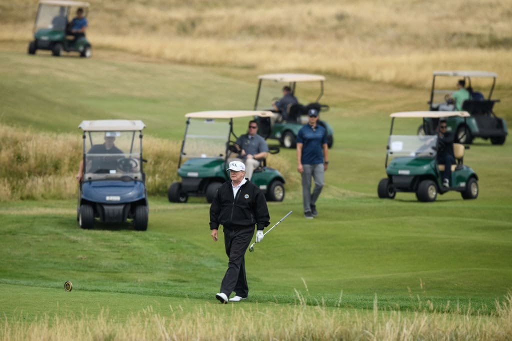 U.S. President Donald Trump, wearing a hat with Trump and USA displayed on it, plays golf at Trump Turnberry Luxury Collection Resort during the President's first official visit to the United Kingdom on July 14, 2018 in Turnberry, Scotland. (Getty Images)