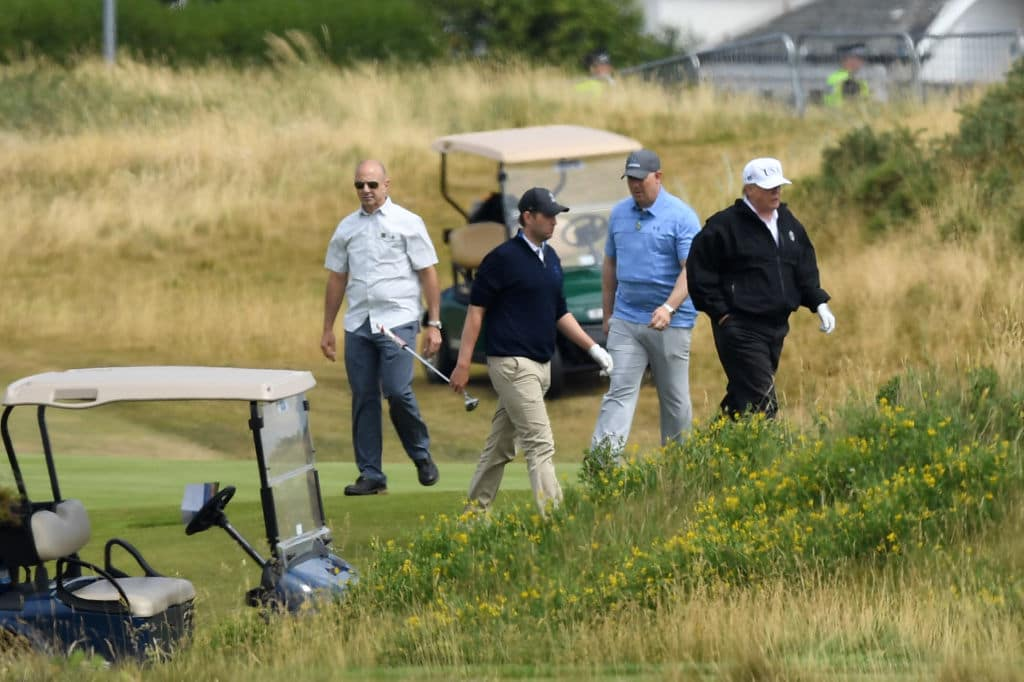 U.S. President Donald Trump (R) and son Eric Trump (2nd-L) play golf at Trump Turnberry Luxury Collection Resort during the President's first official visit to the United Kingdom on July 14, 2018 in Turnberry, Scotland. (Getty Images)
