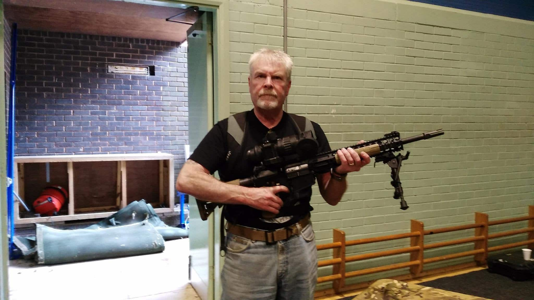 Stephen Searle, 64, is pictured holding a massive rifle (Image: SWNS)