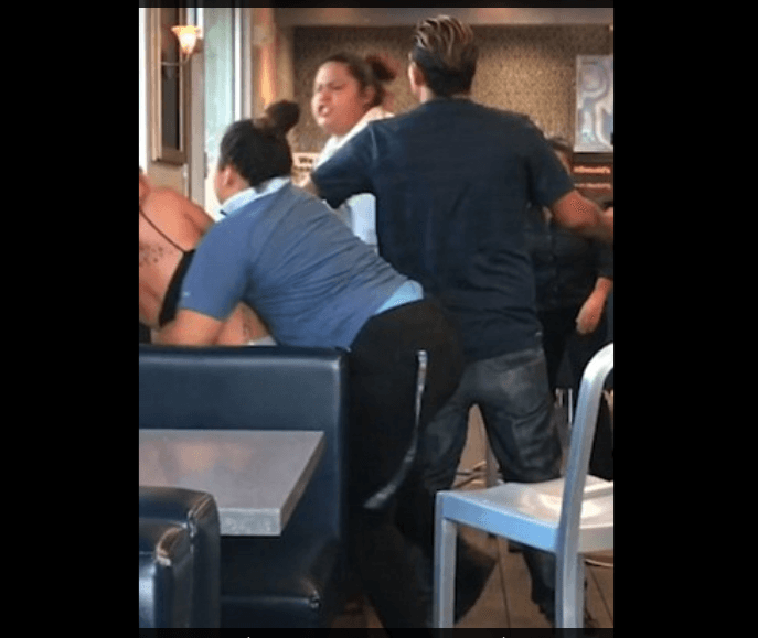 Customers and employee at the eatery can be seen breaking up the brawl. (Youtube screenshot)