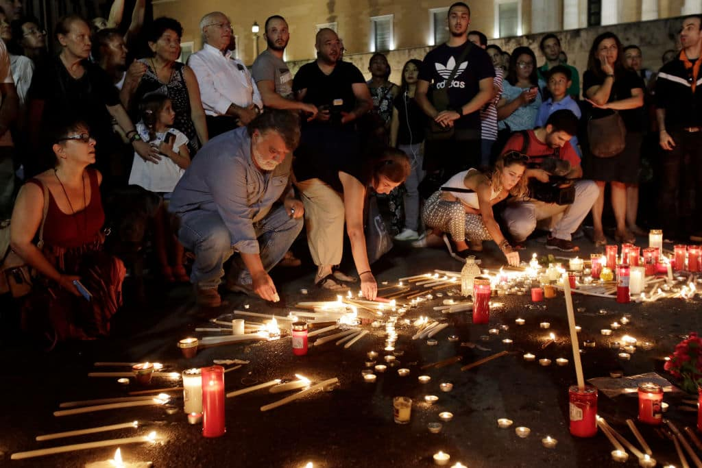 Members of the public light candles outside the Greek Parliament to commemorate the victims of the country's worst ever wildfires on July 30, 2018 in Athens, Greece. (Getty Images)