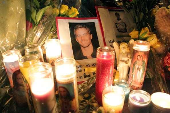 fans pay tribute to actor Paul Walker at the crash site on December 1, 2013 in Valencia, California. (Photo by David Buchan/Getty Images)