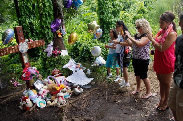 People look on at the Caylee Anthony memorial that has been placed in the area where the 2-year-old child's body was found on July 17, 2011 in Orlando, Florida. (Photo by Joe Raedle/Getty Images)
