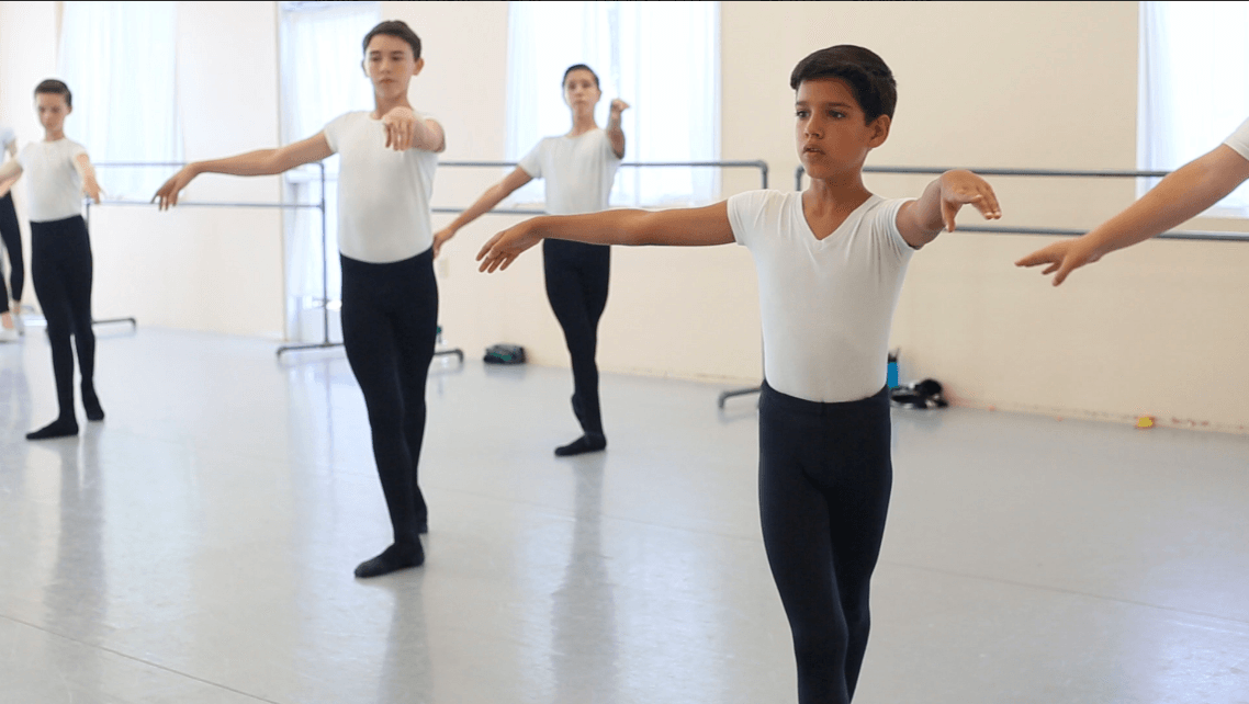 A still from the documentary Danseur shows young boys during a ballet class.