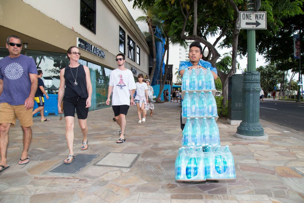 Joel Zane pushs a dolly stacked high with water for his ABC store in preparation for Hurricane Lane on Kalaukaua Ave on Wednesday, August 22, 2018 in Honolulu, Hawaii. (Getty Images)
