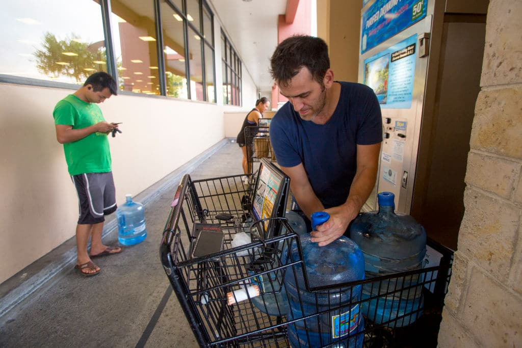 Wenkai He, left, waits his turn to fill up his 3 gallon water jug for just $1.50, while Alex Krivoulian fills three times as many water jugs at Safeway on Kapahulu in preparation for Hurricane Lane on Wednesday, August 22, 2018 in Honolulu, Hawaii. (Getty Images)