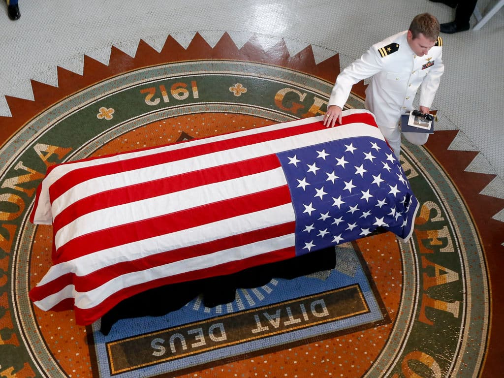 John McCain's son Jack touches the casket during a memorial service at the Arizona Capitol on August 29, 2018 in Phoenix (Photo by Ross D. Franklin-Pool via Getty Images)