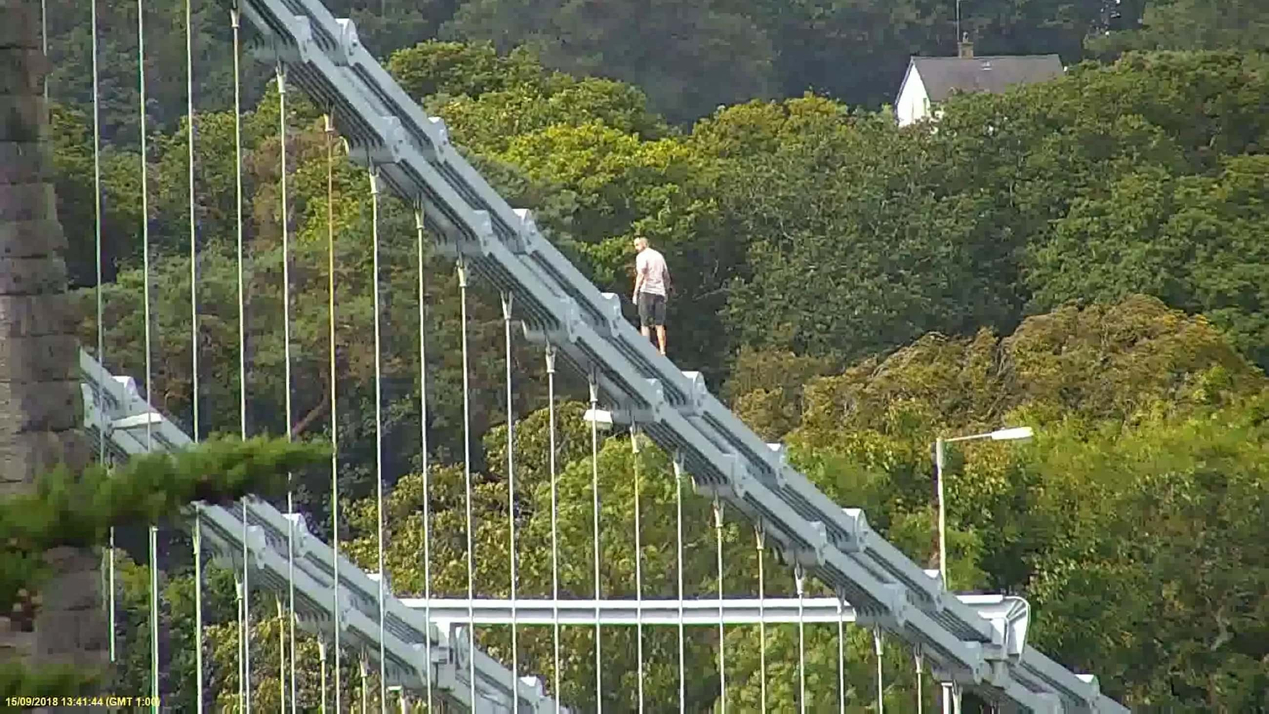 Police had to close off the bridge causing two-hour long tailbacks while Jones walked along the railings with his t-shirt off (SWNS)