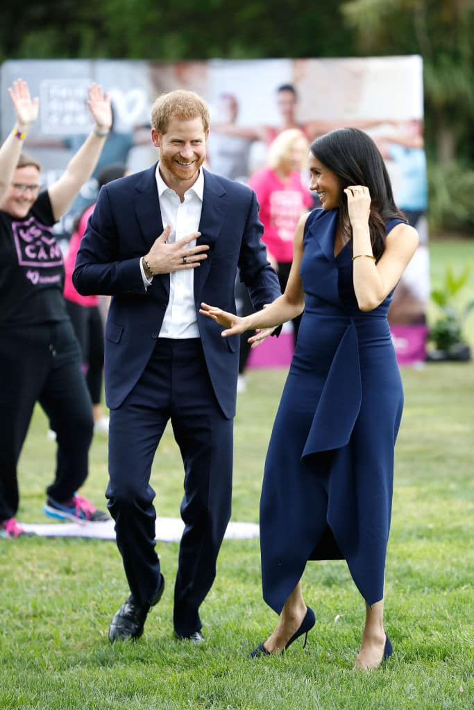 Meghan looked gorgeous in the navy dress which featured a wrap front, cinched-in waist and elegant A-Line skirt with folded detailing (Getty Images)