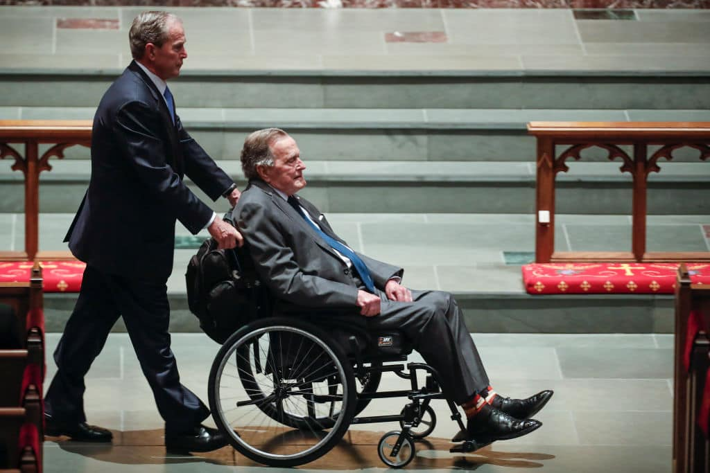 George W. Bush, left, wheels his father, George H.W. Bush into the church for the funeral for former first lady Barbara Bush at St. Martin's Episcopal Church on April 21, 2018 in Houston (Photo by Brett Coomer - Pool/Getty Images)