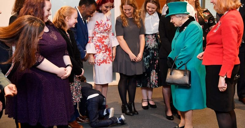 Shy young boy crawls away from Queen Elizabeth at charity event and yells 'bye' before leaving the room