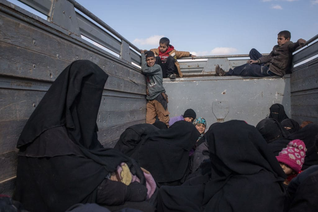 Women and children who have fled fighting in Bagouz look out the back of a truck after stopping at a point on the road so members of the press could interview them before being transported to a camp after they were screened by members of the Syrian Democratic Forces (SDF) at a makeshift screening point in the desert on February 11, 2019 in Bagouz, Syria. (Photo by Chris McGrath/Getty Images)