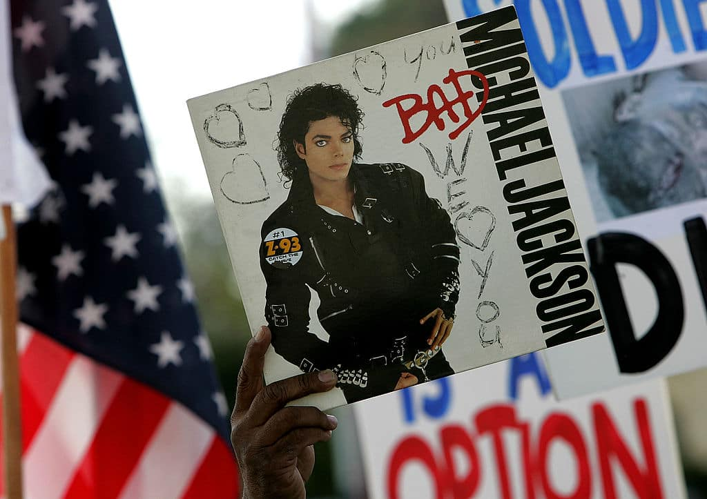 A supporter of singer Michael Jackson holds a copy of Jackson's album 'Bad' as he arrives at the Santa Barbara County Courthouse for another day of proceedings in his child molestation trial May 13, 2005, in Santa Maria California. (Photo by Justin Sullivan/Getty Images)