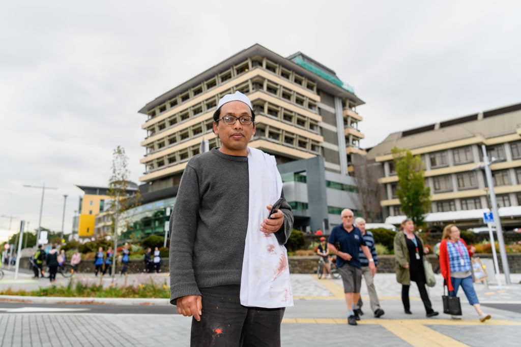 Hamzah Noor Yahaya, a survivor of the shootings at Al Noor mosque, stands in front of Christchurch Hospital at the end of a lockdown and waits to be picked up by his wife on March 15, 2019 in Christchurch, New Zealand. Four people are in custody following shootings at two mosques in the city. The terrorist attack occurred at Al Noor mosque and the Linwood Masjid in Christchurch. (Photo by Kai Schwoerer/Getty Images)